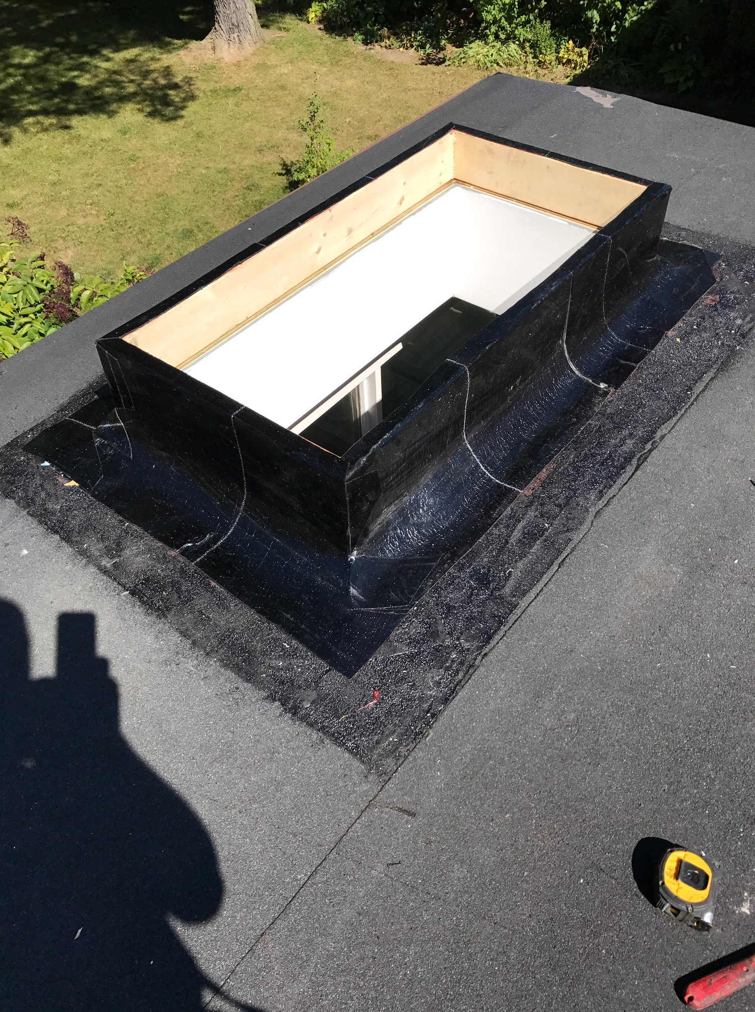 Base membrane flashing on flat roof skylight in North York