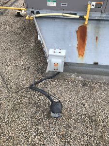 Bitumen sealant at electrical conduit from air conditioning unit on flat roof in Burlington