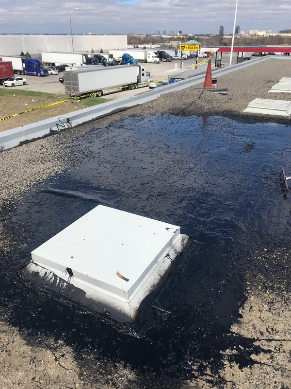 Flat roof repair by Pickering roofing company on industrial building in Pickering
