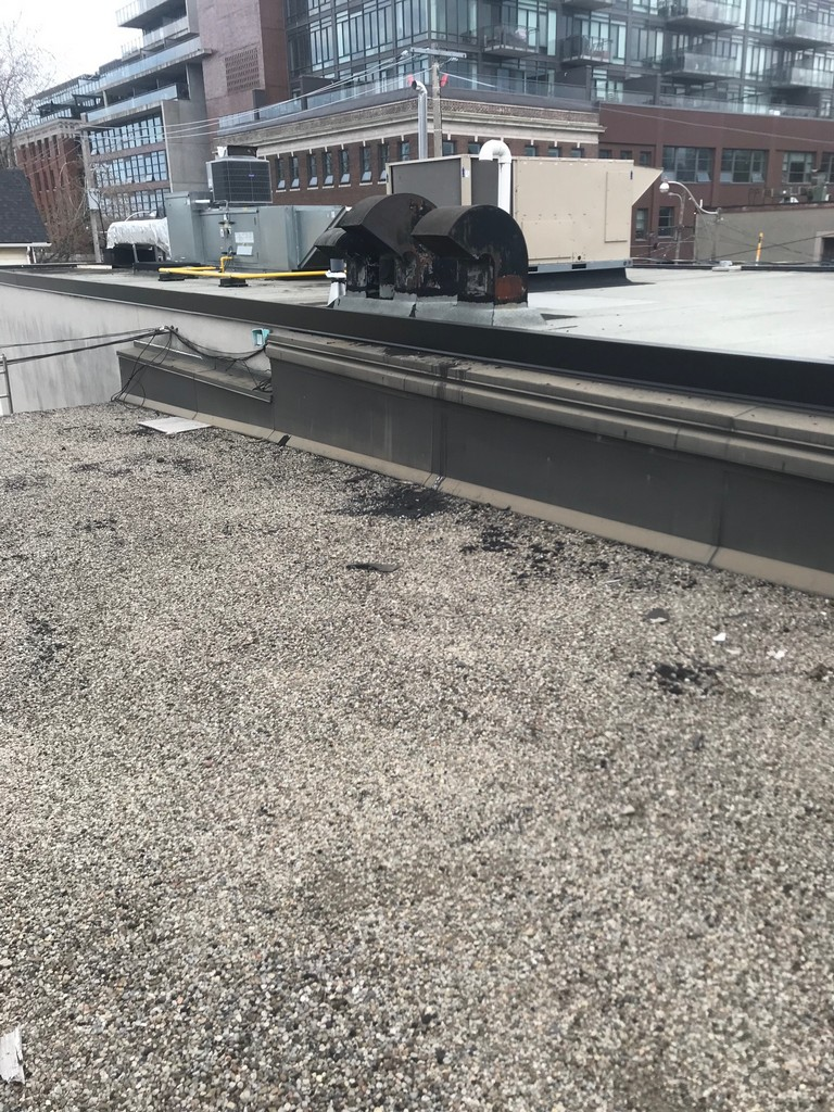 Sealing of metal flashing at wall of commercial flat roof in Scarborough