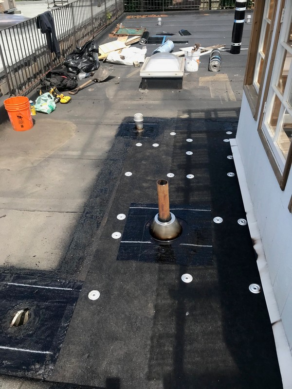 Install of Fiberglas protection board to slope flat roof on property in Toronto