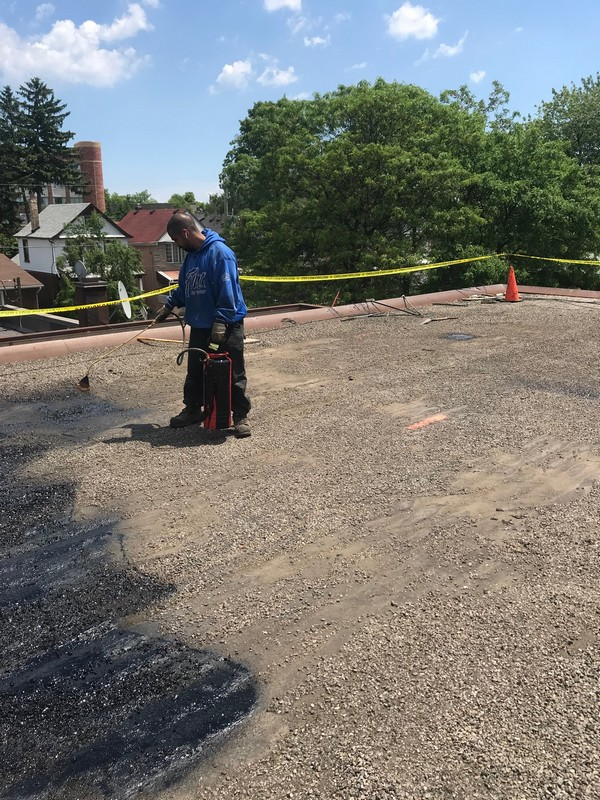Asphalt primer being applied to tar and gravel commercial roof in Scarborough