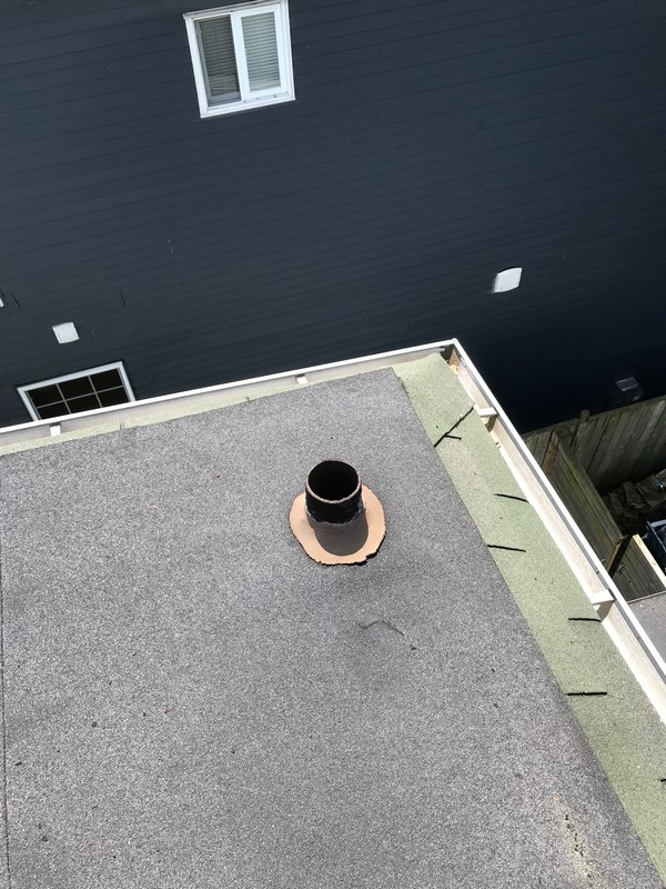 Roof repairs at cast iron plumbing pipe on flat roof in Scarborough