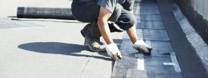 Image of a worker laying down roofing system for flat roofing in construction gear
