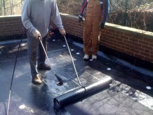 Image of a Metro Roofing worker sealing a flat roof after implementing system